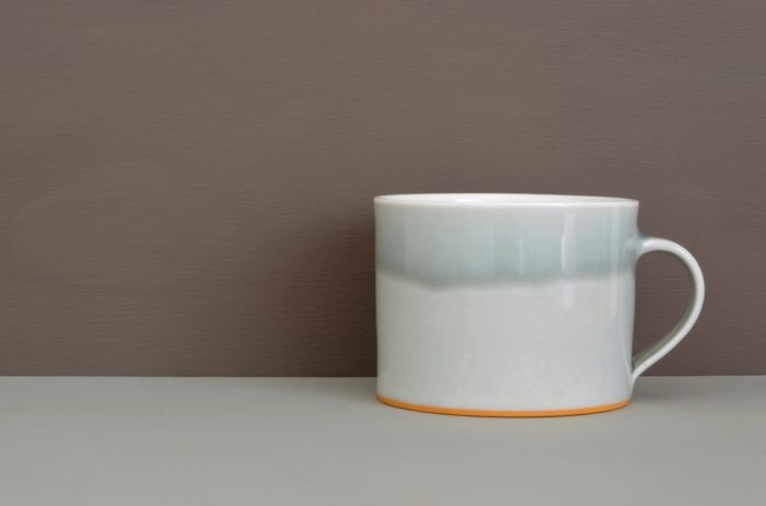 porcelain breakfast mug glazed in grey with orange foot by James and Tilla Waters