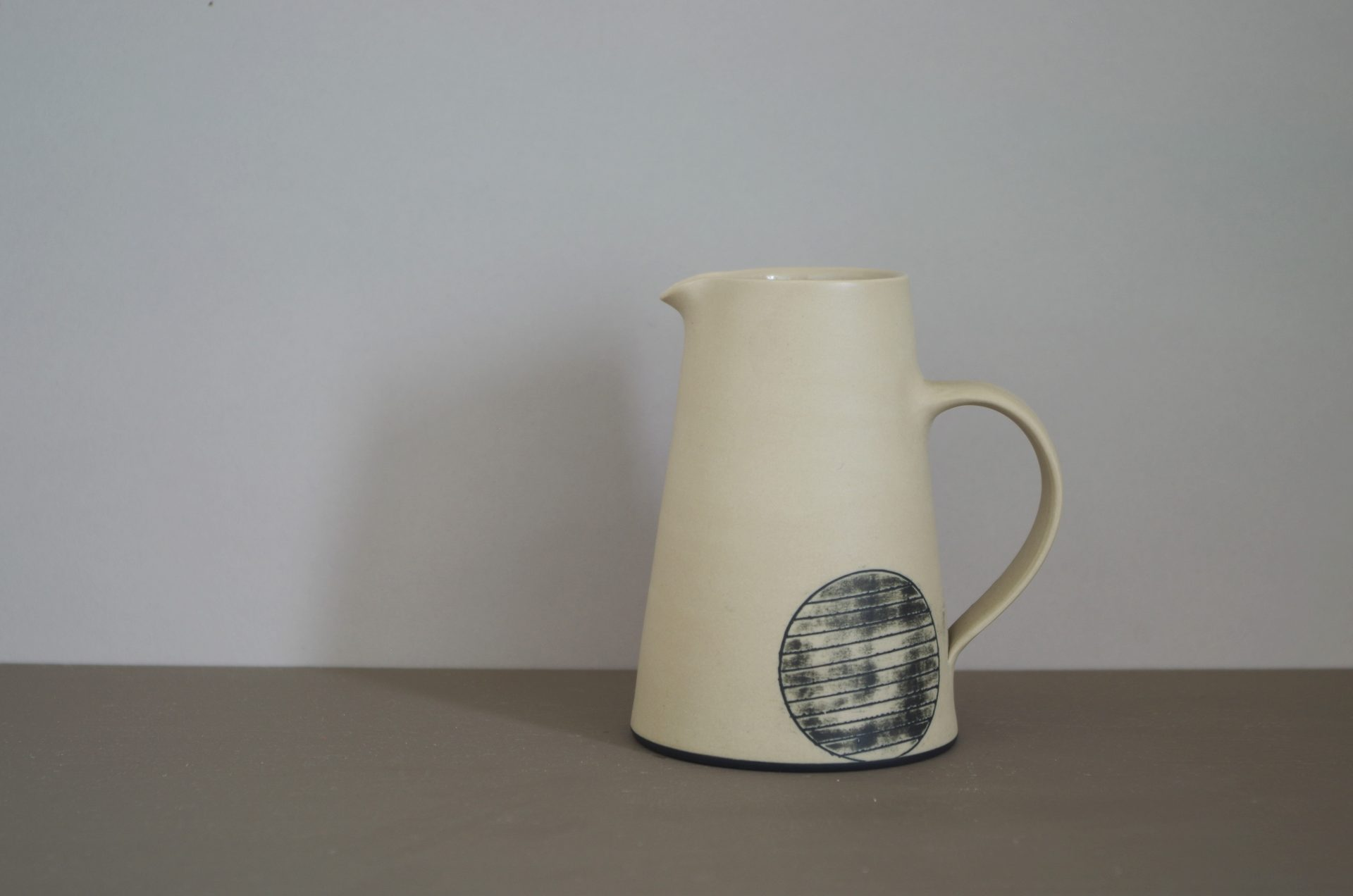 stone coloured jug with black inlaid circle by james and tilla waters
